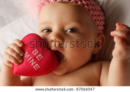 Valentine's day picture of baby chewing on a heart that says Be Mine on white fabric surface - stock photo
