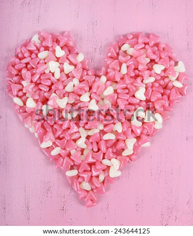 Valentine's Day pink and white jelly candy confectionery in heart shape on pink wood background. - stock photo