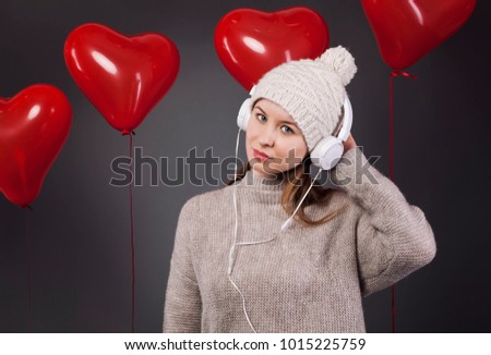 Valentine's Day.Portrait of Smiling Beauty Girl listenning to the music.Bunch of heart shaped air balloons in the background. Love.