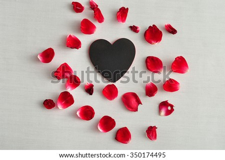 Valentine's day. Red rose petals with a black heart isolated on a white background - stock photo