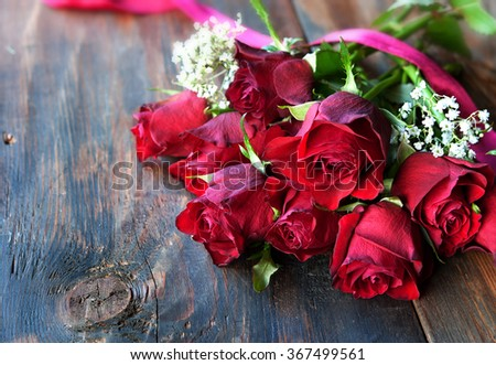Valentine's Day red roses on dark wood background with red ribbon - stock photo