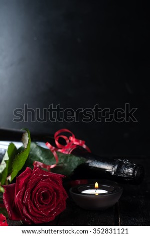 Valentine's day roses and champagne over dark background - stock photo