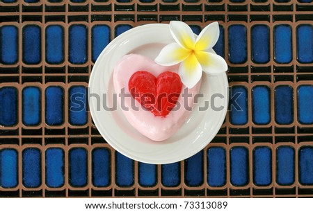 Valentine's day theme - Cake with a beautiful plumeria flower on a blue tile background - stock photo