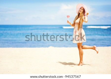 Valentine's day: Young caucasian woman holding lollipop-heart on the beach - stock photo
