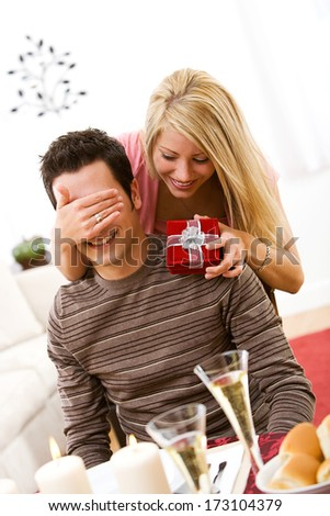 Valentine: Woman Surprises Boyfriend With Gift - stock photo