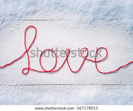 """Valentines background  with snow. Word """"love"""" on white wooden background. Valentines Day background - stock photo"""