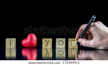 Valentines concept with a man writing with a pen on wooden blocks - I Love You - with a symbolic red heart depicting his Love and commitment