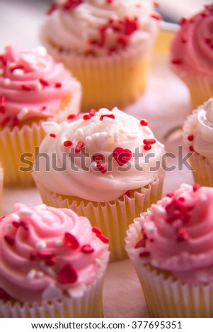 Valentines Cupcakes, small cupcakes with white and pink frosting and red and white heart shape sprinkles.