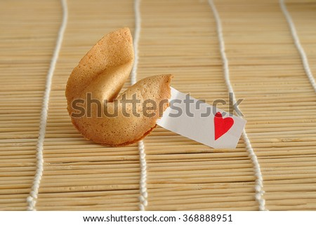 Valentines day. A fortune cookie with a piece of paper with a red heart displayed on a black background - stock photo