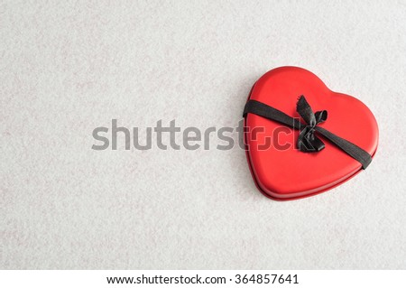 Valentines day. A red heart tied with a black ribbon isolated against a white background