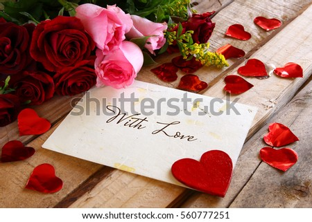 Valentines day background. Beautiful bouquet of roses next to the letter on wooden table