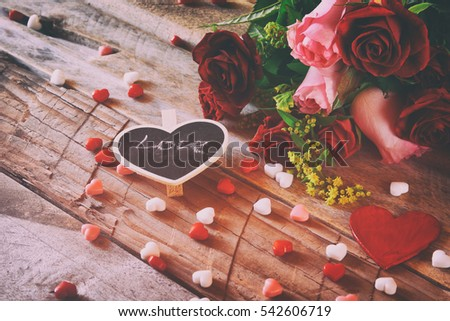 Valentines day background. Red hearts and roses on wooden table. Filtered and toned image