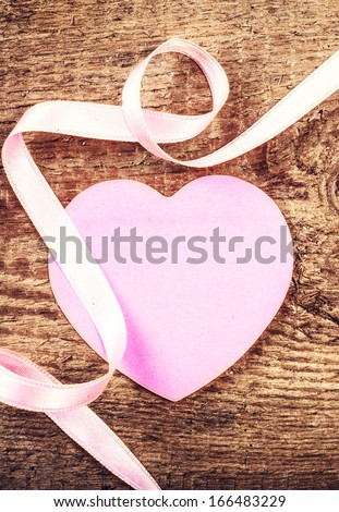 Valentines Day background with  copyspace. Paper Heart and beautiful gentle ribbon on wooden rustic board . Love concept in retro style. Valentines Day Card.