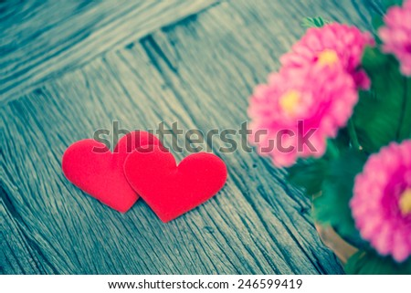 Valentines Day background with Fabric valentine heart on grunge wood table with gebera flower foreground.. Retro filter. - stock photo