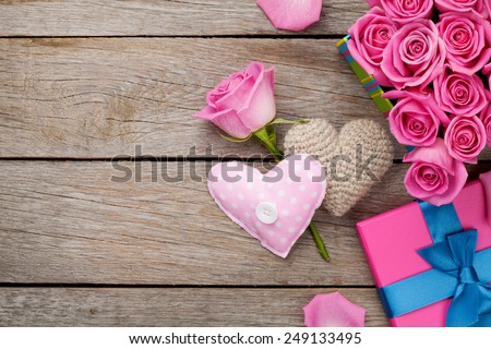 Valentines day background with gift box full of pink roses and handmaded toy hearts over wooden table. Top view with copy space - stock photo