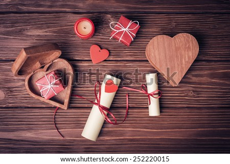 Valentines day background with gift boxes, candle, rolled paper and red heart - stock photo