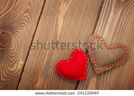 Valentines day background with handmade toy hearts over wooden table - stock photo