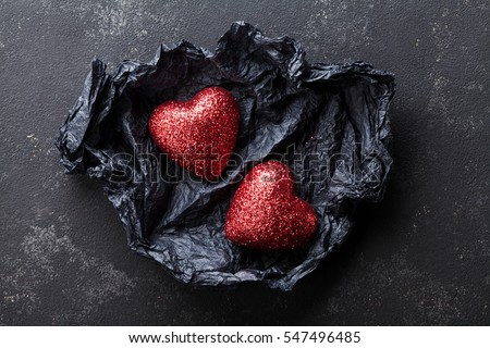 Valentines day background with pair of shiny heart in black paper from above.
