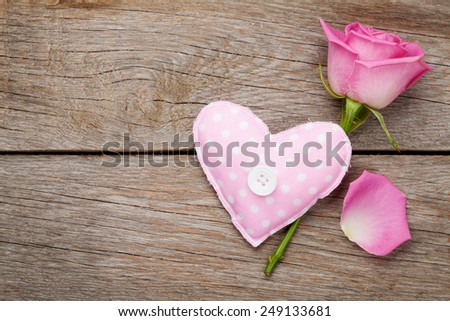 Valentines day background with pink rose and handmaded toy heart over wooden table. Top view with copy space - stock photo
