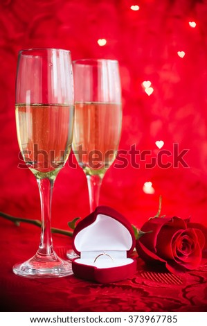 Valentines day background with two glasses of champagne, ring and rose on red background with bokeh in heart form. Marriage Proposal. Romantic table setting. Presents for woman on Valentine's Day. - stock photo