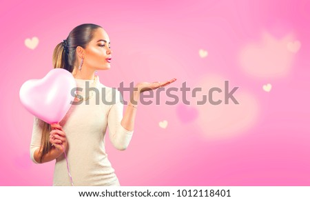 Valentines Day Beauty girl with pink heart shaped air balloon pointing hand, blows hearts on pink background. Beautiful Happy Young woman presenting products. Holiday party, birthday. Wide angle