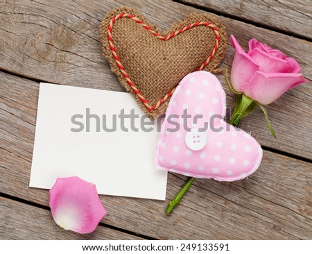 Valentines day blank greeting card or photo frame with handmaded toy hearts and pink rose over wooden table. Top view - stock photo