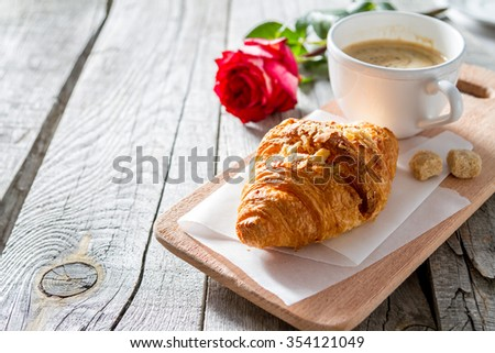 Valentines day breakfast - delicious fresh croissants with coffee and rose, copy space - stock photo
