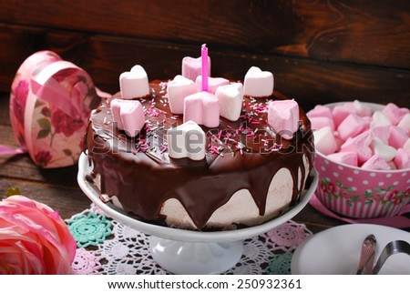 valentines day cake with chocolate glaze and heart shaped marshmallow decoration on wooden table - stock photo