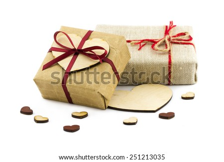 Valentines Day concept. Gift boxes with red ribbon and small wooden hearts isolated on white background - stock photo