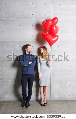 Valentines day concept. Loving couple with red heart balloons on gray background.