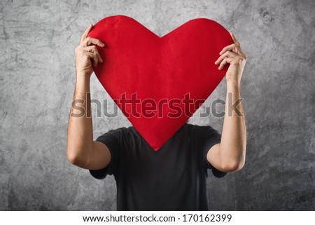 Valentines day concept. Man holding big red heart in front of his face.