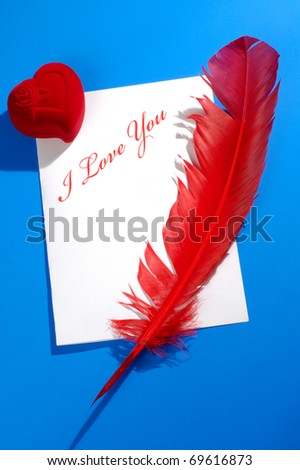 Valentines Day concept. Red heart-shaped jewelry gift box and a red quill on a letter with I love you written on it. Conceptual still life isolated on blue background - stock photo