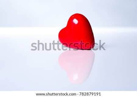 Valentines day conceptual image with one red heart shaped object with reflection against white