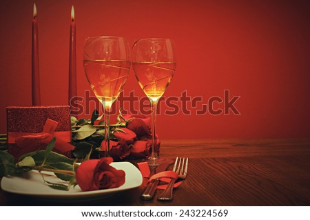 Valentines day: glasses of vine, red roses, candles and present a retro photo