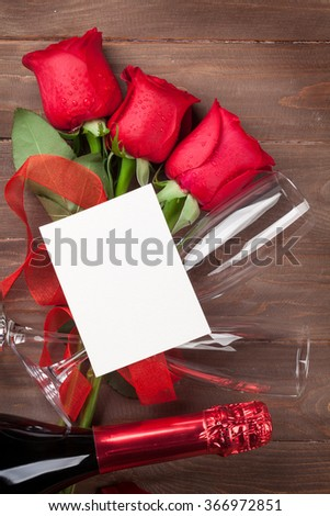 Valentines day greeting card, champagne and red roses on wooden table. Top view with copy space - stock photo