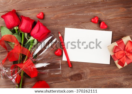 Valentines day greeting card, champagne glasses and red roses on wooden table. Top view with copy space - stock photo