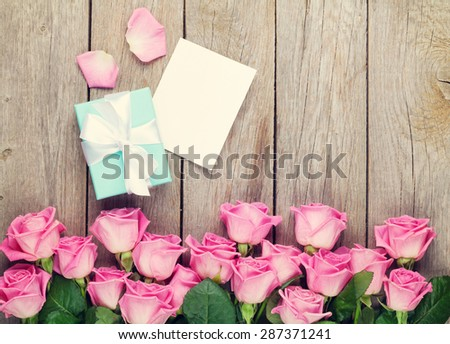 Valentines day greeting card, gift box and pink roses over wooden table. Top view - stock photo