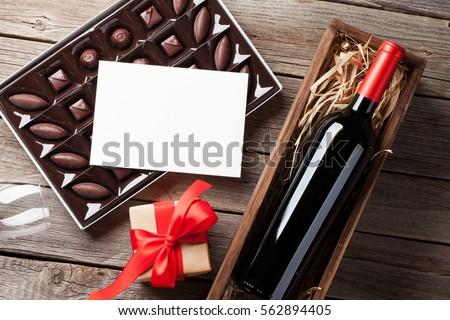 Ngày Valentine thiệp chúc mừng.  Rượu vang đỏ, hộp quà tặng và hộp chocolate trên bàn gỗ.  Top xem với không gian cho lời chúc mừng của bạn