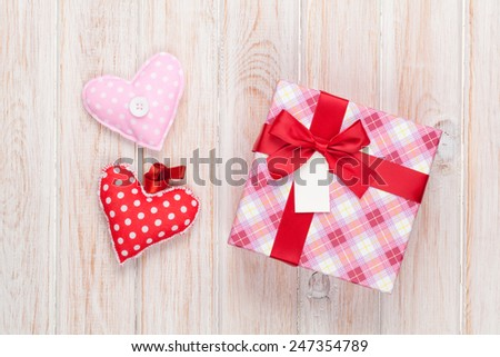 Valentines day handmaded toy hearts and gift box over white wooden table - stock photo