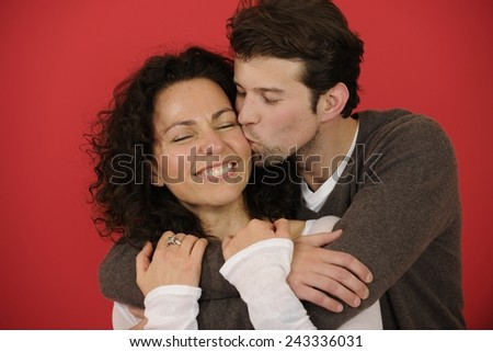 Valentines day: Happy man kissing woman on red background - stock photo