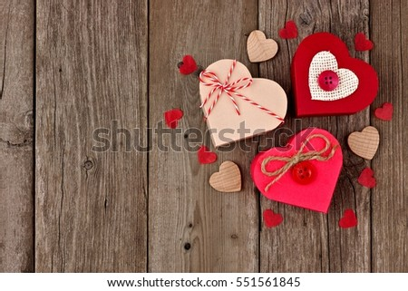 Valentines Day heart shaped gift boxes with red and burlap trim in a cluster over wood
