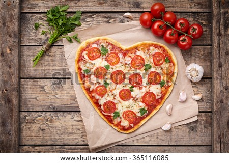 Valentines day heart shaped pizza margherita vegetarian love concept with mozzarella. tomatoes, parsley and garlic on vintage wooden table background. - stock photo