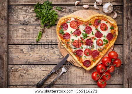Valentines day heart shaped pizza with pepperoni, cherry tomatoes, mozzarella and parsley on vintage wooden table background. Symbol of love.