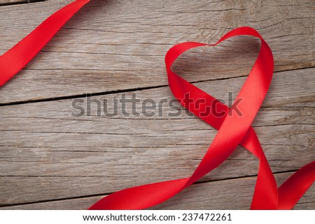Valentines day heart shaped ribbon over wooden table background with copy space - stock photo