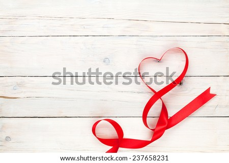 Valentines day heart shaped ribbon over wooden table background with copy space