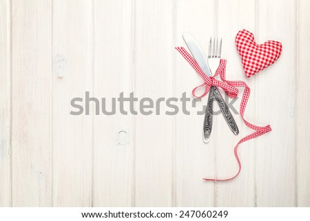 Valentines day heart shaped toy gift and silverware. View from above over white wooden table with copy space - stock photo