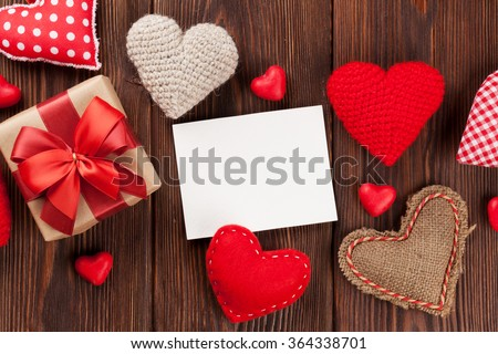 Valentines day hearts, candies, gift box and greeting card over wooden background. Top view with copy space - stock photo
