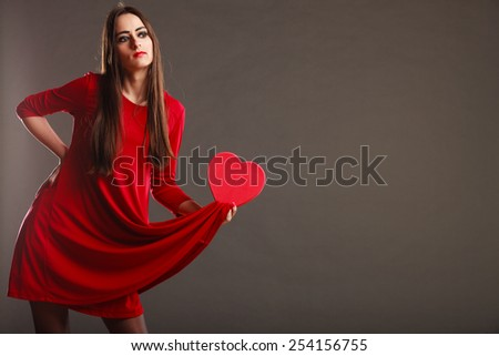 Valentines day, love, romance concept. Brunette woman long hair girl in red dress holding heart shaped gift box dark gray background - stock photo