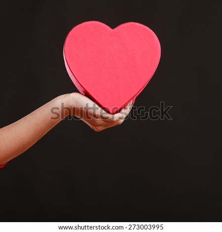 Valentines day, love, romance concept. Woman hand holding heart shaped gift box on dark gray background. - stock photo