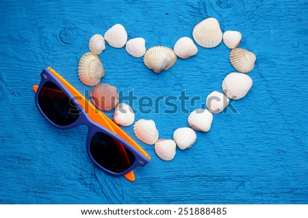 valentines day picture. sunglasses and shells on shape of heart on wooden blue background with place for text - stock photo